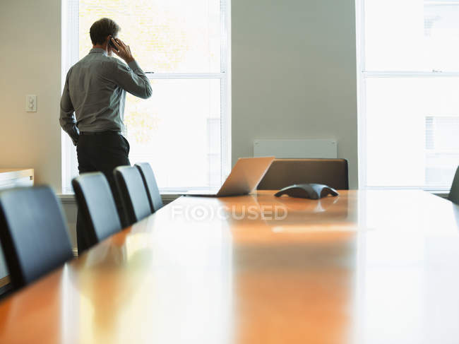 Businessman talking on cell phone in conference room — Stockfoto