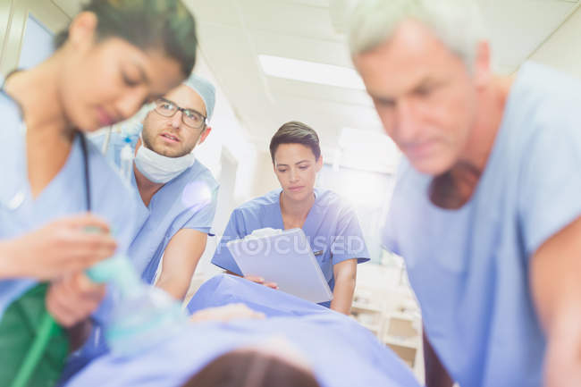 Surgeons with clipboard pushing patient on stretcher in hospital corridor — Stock Photo