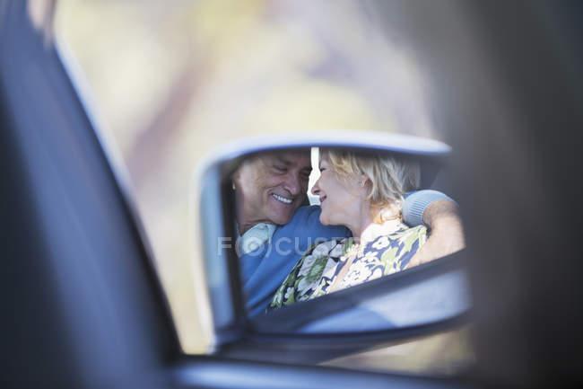 Spiegelreflex eines Paares, das sich im Auto umarmt — Stockfoto