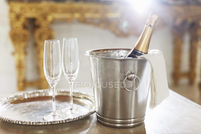 Шампанське в срібло відро поруч із шампанське флейти — стокове фото