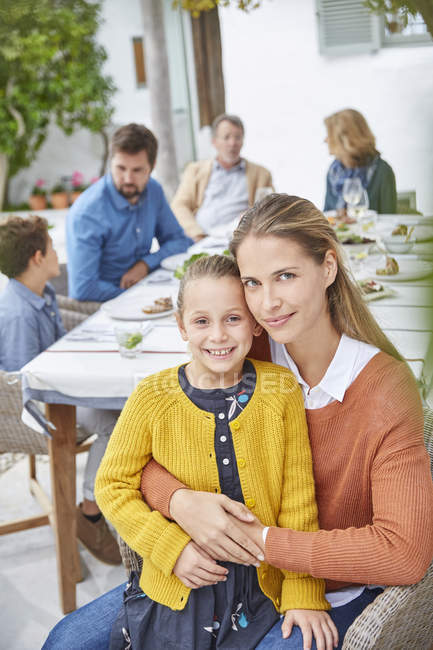 Portrait mother and daughter enjoying patio lunch with family — Stock Photo