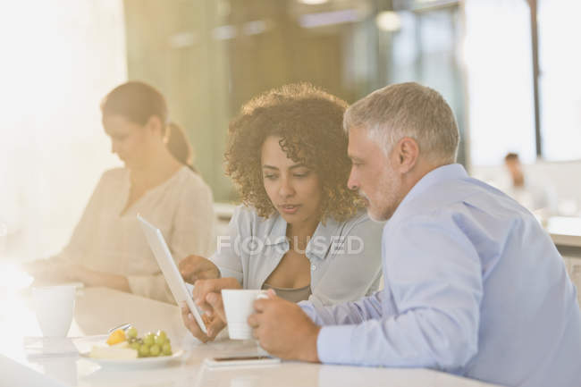 Business people drinking coffee and using digital tablet — Stock Photo