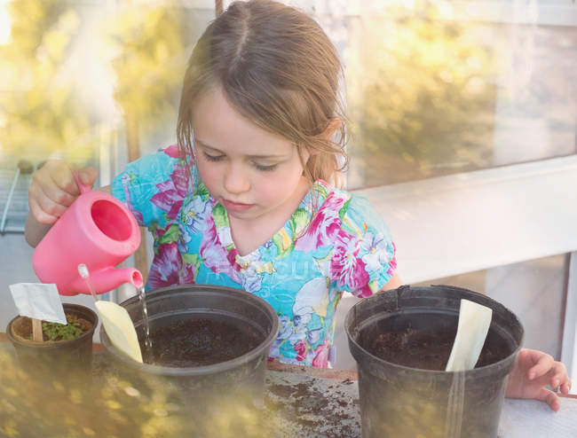 Girl watering seedlings in flowerpots with tiny pink watering can — Stock Photo