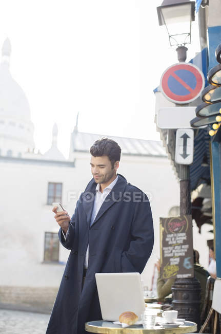 Geschäftsmann mit Handy im Straßencafé — Stockfoto