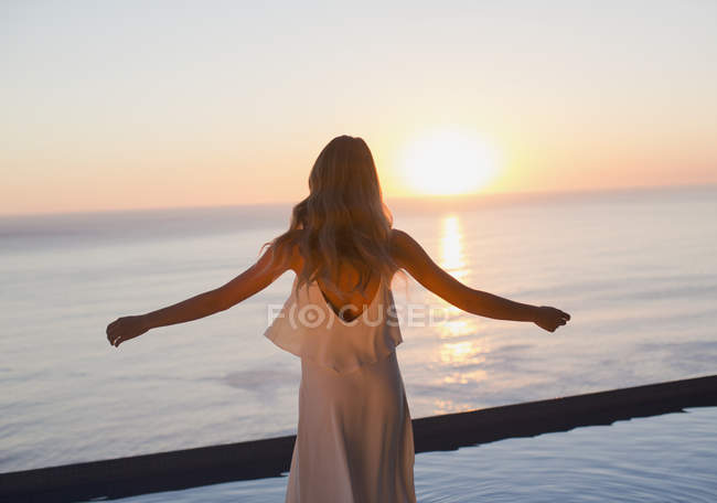 Woman with arms outstretched watching tranquil sunset view over ocean horizon — Stock Photo