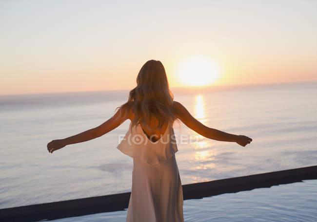 Mulher com os braços esticados, assistindo tranquila vista por do sol sobre o horizonte do oceano — Fotografia de Stock