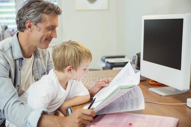 Отец и сын работают в домашнем офисе — стоковое фото