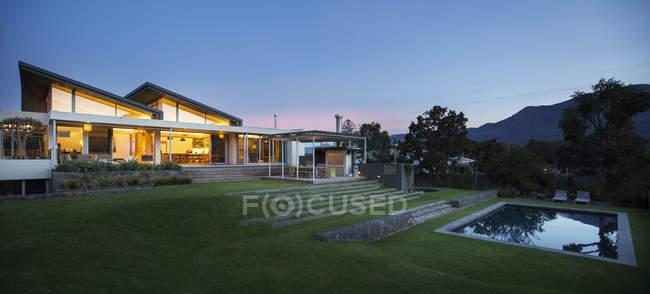 Iluminada casa moderna além do quintal e piscina à noite — Fotografia de Stock