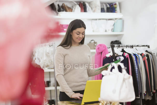 Clothing shop owner taking inventory with clipboard and laptop — Stock Photo