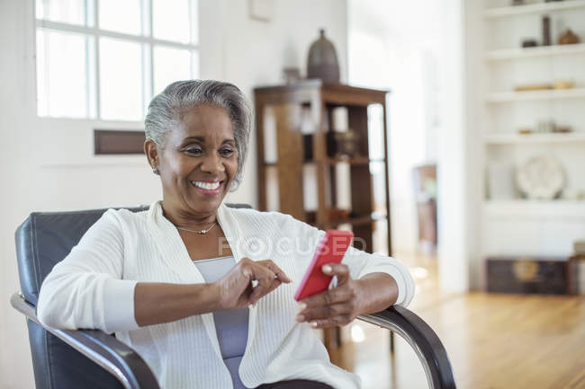 Happy senior woman text messaging with cell phone in living room — Stock Photo