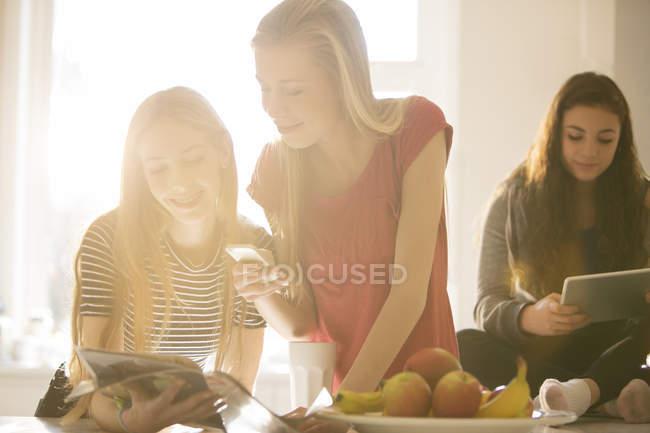 Adolescenti che utilizzano il telefono cellulare e tavolette digitali — Foto stock