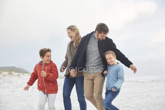 Família brincalhona na praia de inverno juntos — Fotografia de Stock