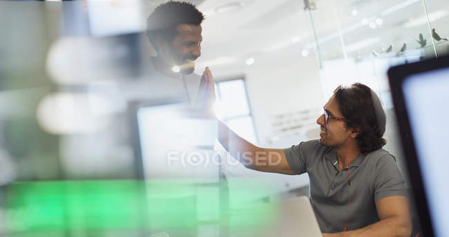 Creative businessmen high fiving in office — Stock Photo