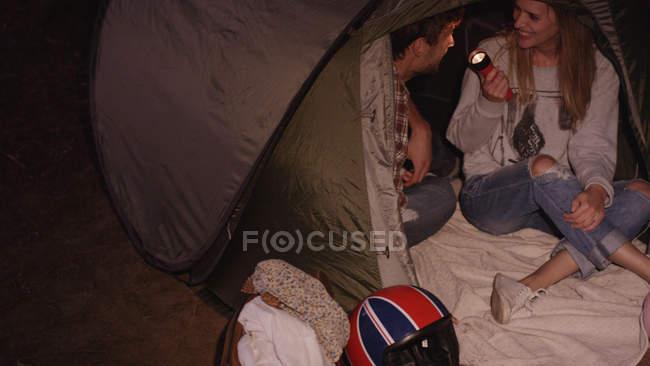 Молодая пара с фонариком внутри палатка — стоковое фото