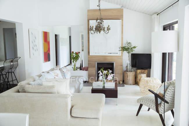 Диван, журнальный столик и камин в современной гостиной — стоковое фото
