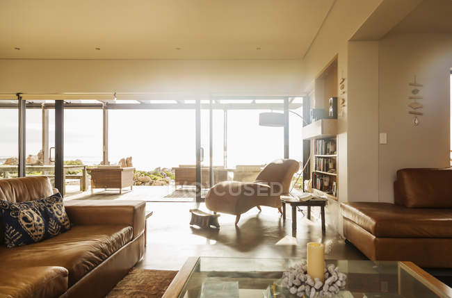 Sunny home showcase living room with open patio doors — Stock Photo