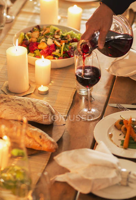 Donna versando vino a cena — Foto stock