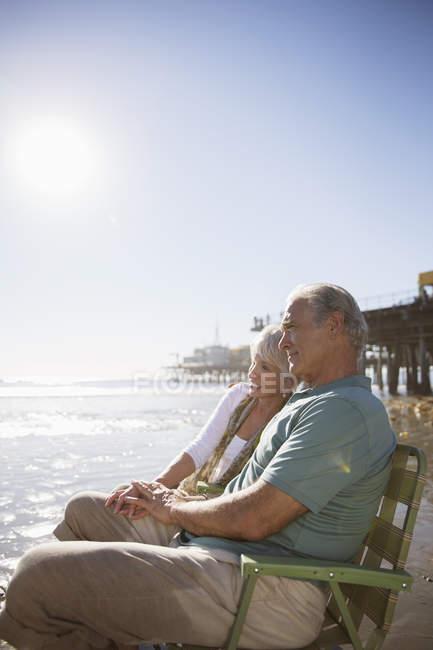 Seniorenpaar entspannt in Liegestühlen am Strand — Stockfoto