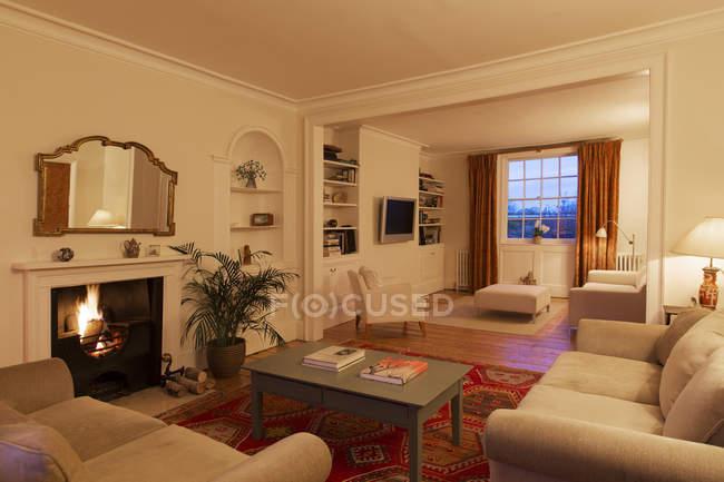 Beleuchteten Wohnzimmer mit Kamin — Stockfoto