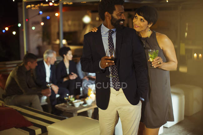 Couple hugging at party — Stock Photo
