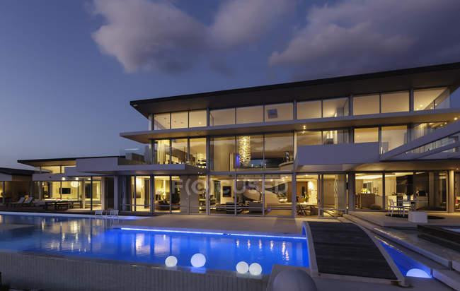 Иллюминированная современная витрина роскошного дома с бассейном по ночам — стоковое фото