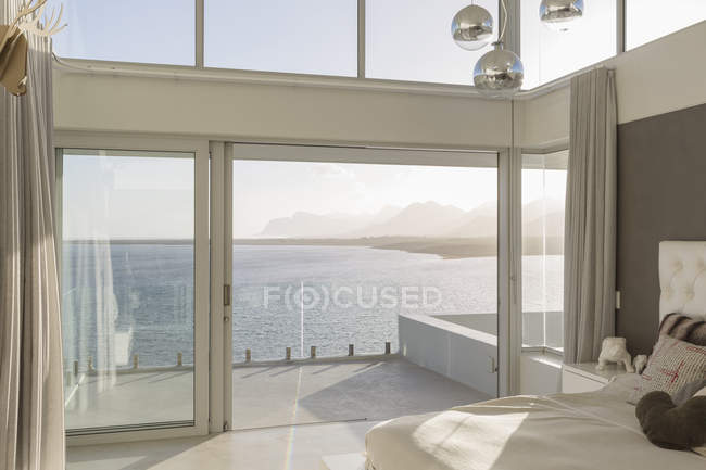 Sunny, tranquil modern luxury home showcase interior bedroom with ocean view — Stock Photo