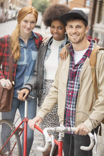 Friends smiling together on city street — Stock Photo