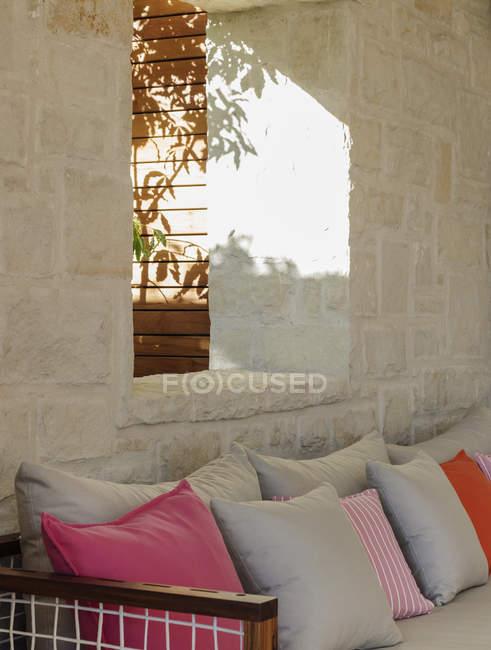 Каменная стена за патио скамейке с подушками — стоковое фото