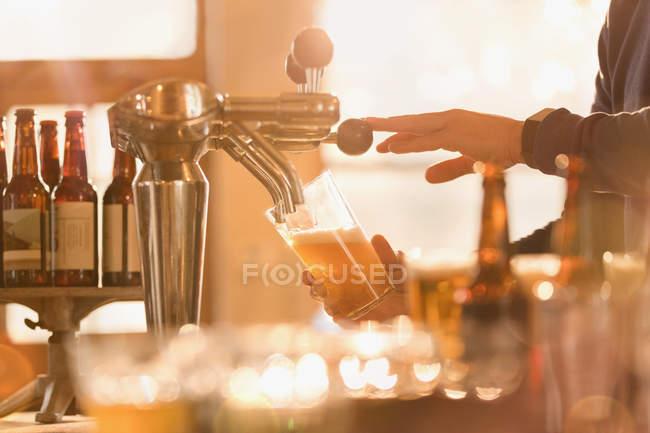 Кадроване зображення Бармен розливу пива з пивом крана позаду бар — стокове фото