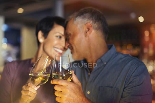 Casal afetuoso brindar copos de vinho branco no bar — Fotografia de Stock