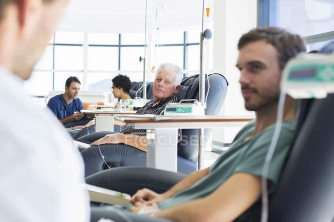 Врачи говорят пациентов, получающих лечение в больничной палате — стоковое фото