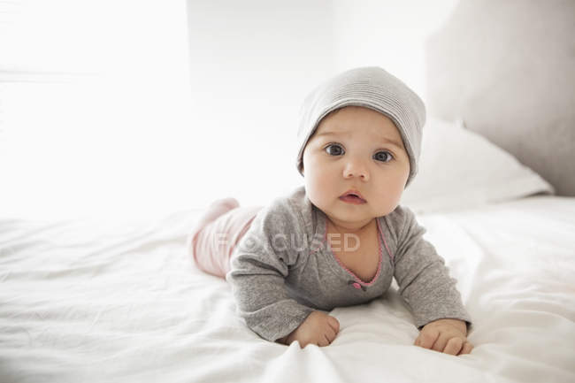 Дівчинку в капелюсі, лежачи на ліжку — стокове фото