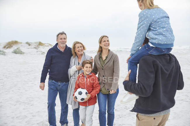 Multi-generation family with soccer ball on winter beach — Stock Photo