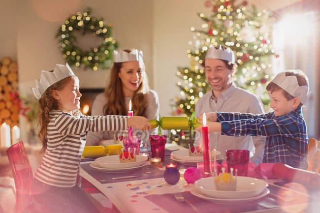 Семья в бумажных коронах тянет рождественский крекер за обеденный стол — стоковое фото