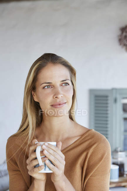 Serene woman drinking coffee and looking away on patio — Stock Photo