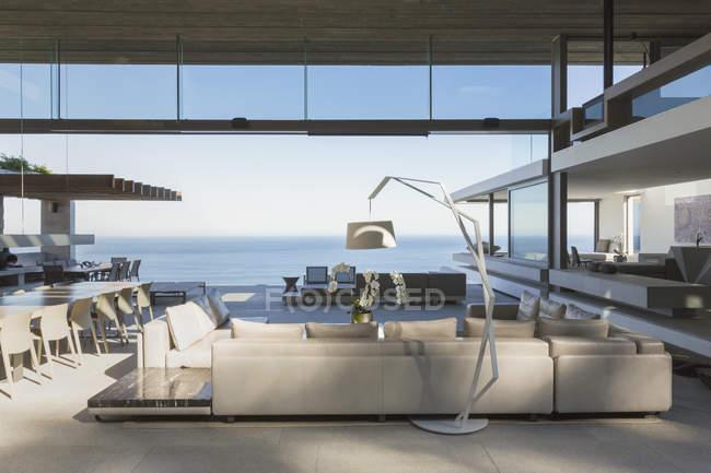 Современные, роскошные дома витрина интерьер гостиной открыты для видом на океан — стоковое фото