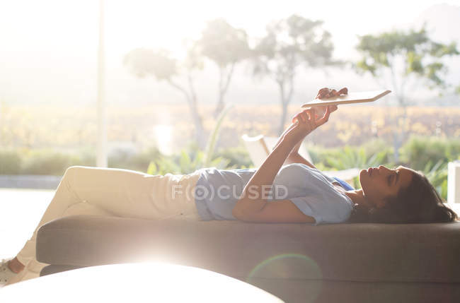 Woman laying on chaise lounge using digital tablet on sunny patio — Stock Photo
