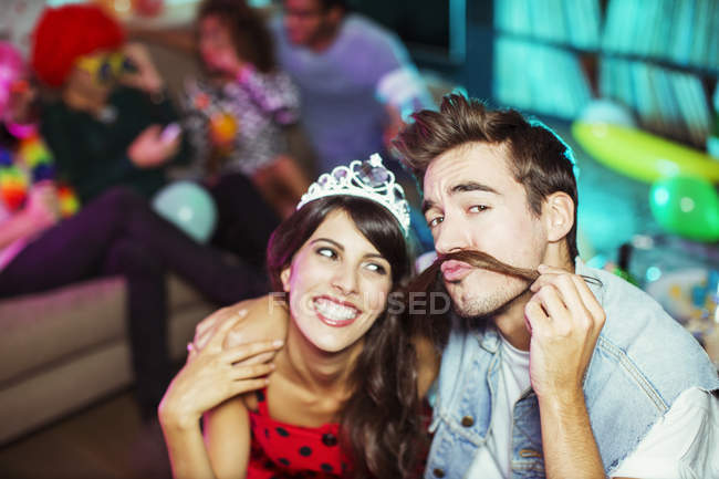Uomo che gioca con la serratura di ragazze come i baffi alla festa — Foto stock