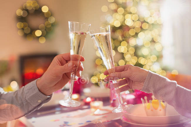 Couple toasting champagne flutes at Christmas dinner table — Stock Photo