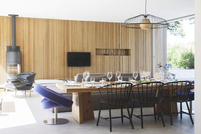 Mesa de comedor, sofás y televisión en salón abierto y comedor - foto de stock