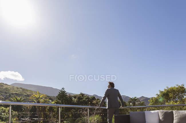 Бизнесмен, стоящий на балконе патио под солнечным голубым небом — стоковое фото