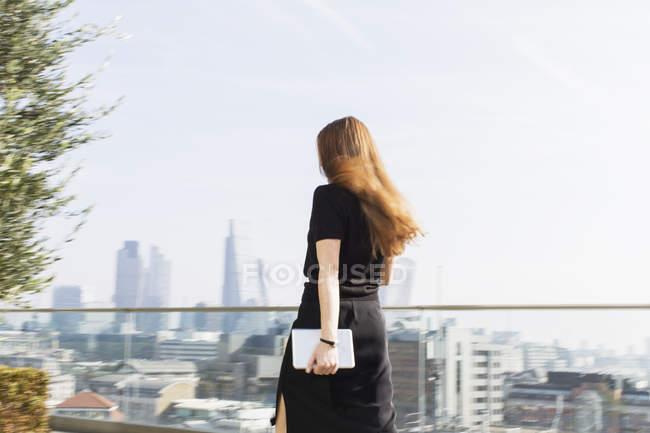 Businesswoman with digital tablet walking on urban balcony — Stock Photo