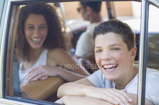 Familia moderna feliz montando en coche juntos - foto de stock