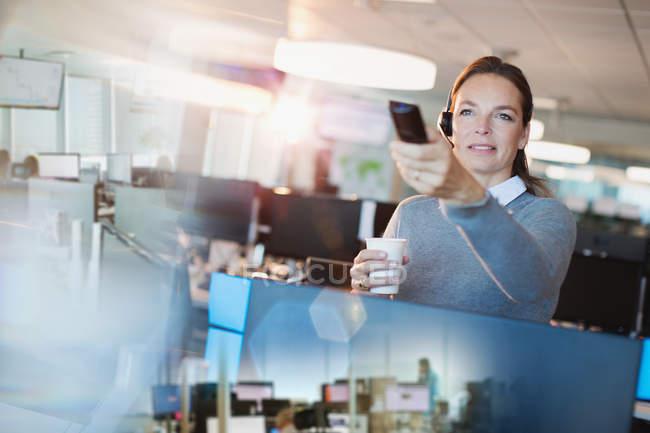 Femme d'affaires à l'aide de la télécommande, boire du café au bureau — Photo de stock