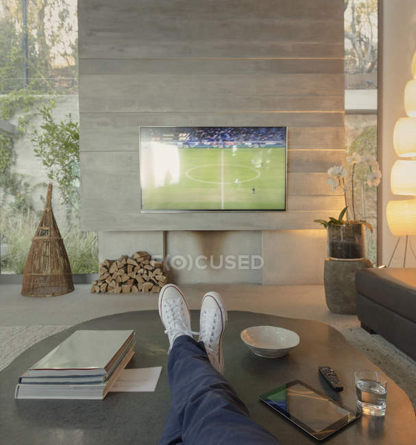 Personal perspective man watching soccer on TV in living room — Stock Photo