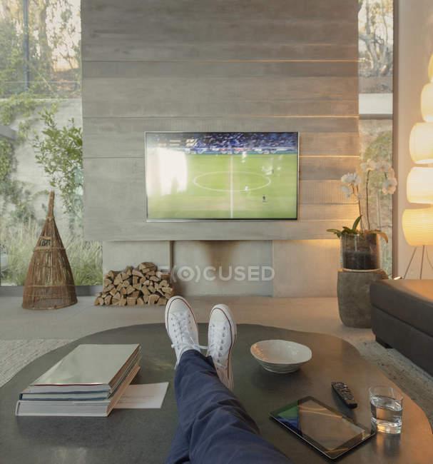 Prospettive personali uomo guardando il calcio in TV in salotto — Foto stock