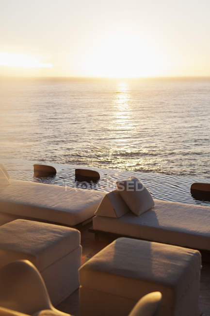 Sofas and infinity pool overlooking ocean — Stock Photo
