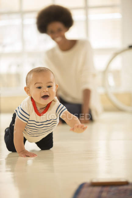 Mother watching baby boy crawl on floor at home — Stock Photo