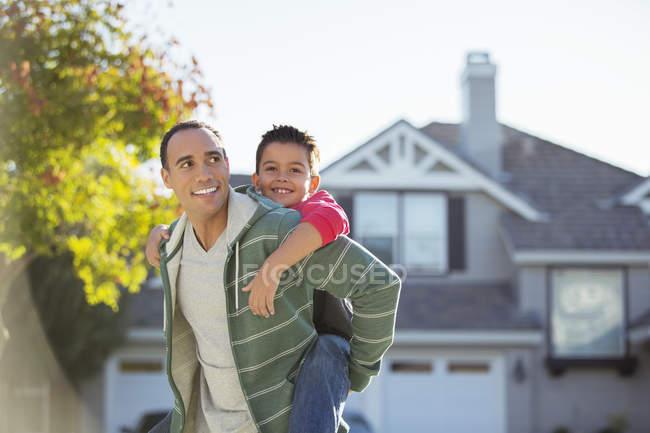 Father piggybacking son outdoors — Stock Photo
