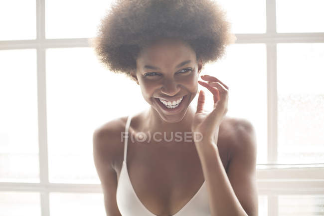 Smiling woman in bra standing by window — Stock Photo